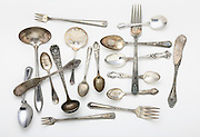 Antique tarnished silverware on white background.