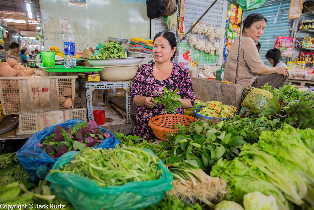 28 MARCH 2012 - HO CHI MINH CITY, VIETNAM:   Produce vendors in the Ben Thanh Market in Ho Chi Minh City, Vietnam. Ben Thanh Market is a large market in the downtown area of Ho Chi Minh City (Saigon), Vietnam in District 1. The market is one of the earliest surviving structures in Saigon and one of the city's landmarks, popular with tourists seeking local handicrafts, textiles,ao dais (Vietnamese traditional dresses), and souvenirs, as well as local cuisine. The market developed from informal markets created by early 17th century street vendors gathering together near the Saigon River. The market was formally established by the French colonial powers in 1859. This market was destroyed by fire in 1870 and rebuilt to become Saigon's largest market. In 1912 the market was moved to a new building and called the New Ben Thanh Market to distinguish over its predecessor. The building was renovated in 1985.    PHOTO BY JACK KURTZ
