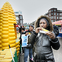 Nederland, Rotterdam , 11 december 2010..Multiculturele samenleving van rotterdam..antilliaanse en Surinaamse bezoekers tijdens zaterdagmarkt op het Afrikaanderplein eten mais bij een turkse mais stand..Clients at a corn stand at the saturday market in Rotterdam Afrikaanderplein.