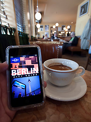 Tourist using e-book travel guide to Berlin in famous Cafe Einstein on Unter den Linden in Berlin Germany