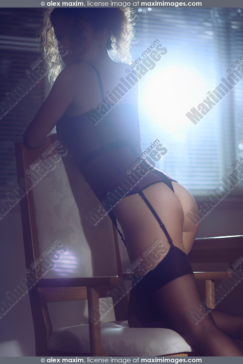 Sensual boudoir portrait of a beautiful sexy woman in a corset and stockings leaning on a chair by a window in a dark room lit by a bright street light at night