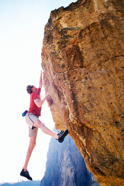 A young man making a jumping / lunging move on a rock climb at Smith Rock State Park, Orgeon, USA.