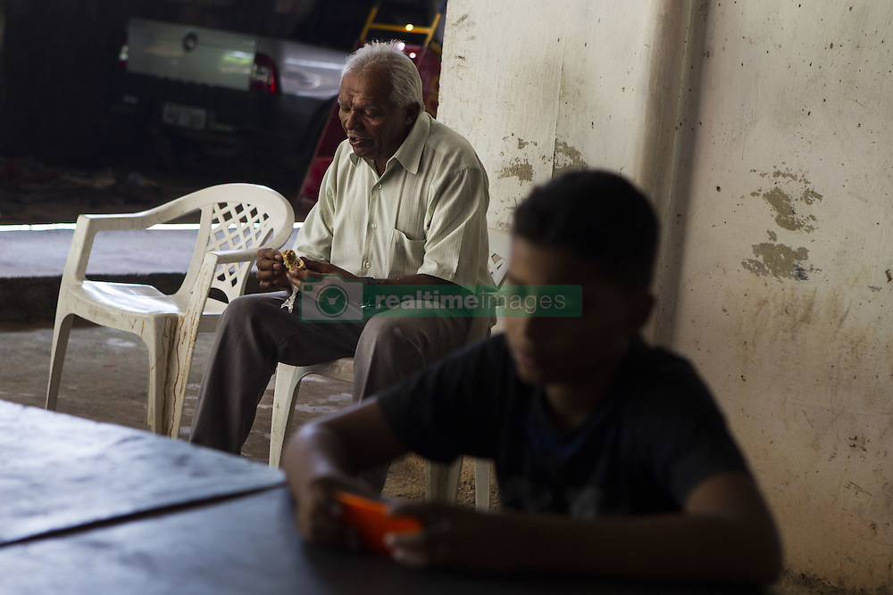 October 9, 2016 - Boa Viagem, Brazil - Occasionally Mr. José receives a visit from his family, but he said it is very rare that this to happen. In this photo he eats a sweet while his grandson, Albert, accesses the phone.  José Belmiro dos Santos is 84 years old, married to Rosalia Maria da Conceição and has nine children. He is retired since 1997 and works in a parking taking care of vehicles. The parking lot is situated in an abandoned building in Boa Viagem, in Recife, Pernambuco state, Brazil.Mr. José has to live in the building and can only visit family once a month. He thinks it's dangerous, because the parking lot is located inside a slum, but need to earn cash and stay home another person can take his job.Mr. José is part of a national statistic that indicates an increase in the number of pensioners who return to work in Brazil, 5.9% in the first quarter of 2012 to 6.5% in the second quarter 2016 (data from the Brazilian Institute of geography and Statistics), due to the current economic crisis.The government of the current President Michel Temer has as one of the goals the approval of Welfare Reform, thus ensuring clearer rules for retirement and the increase in the contribution to the public coffers. The approval of new rules for retirement might take the Brazil of the crisis and increase a government approval rating scored by polemics and an impeachment questioned by the opposition. (Credit Image: © Diego Herculano/NurPhoto via ZUMA Press)