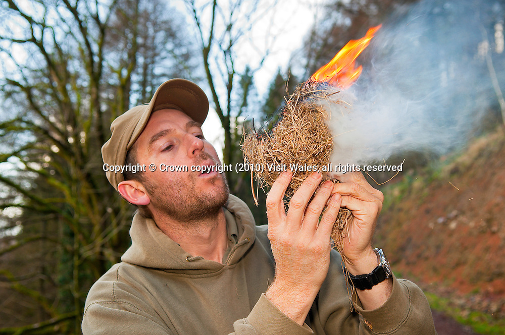 Man lighting fire with dry grasses<br /> Survival skills<br /> Bushcraft<br /> Activities And Sports