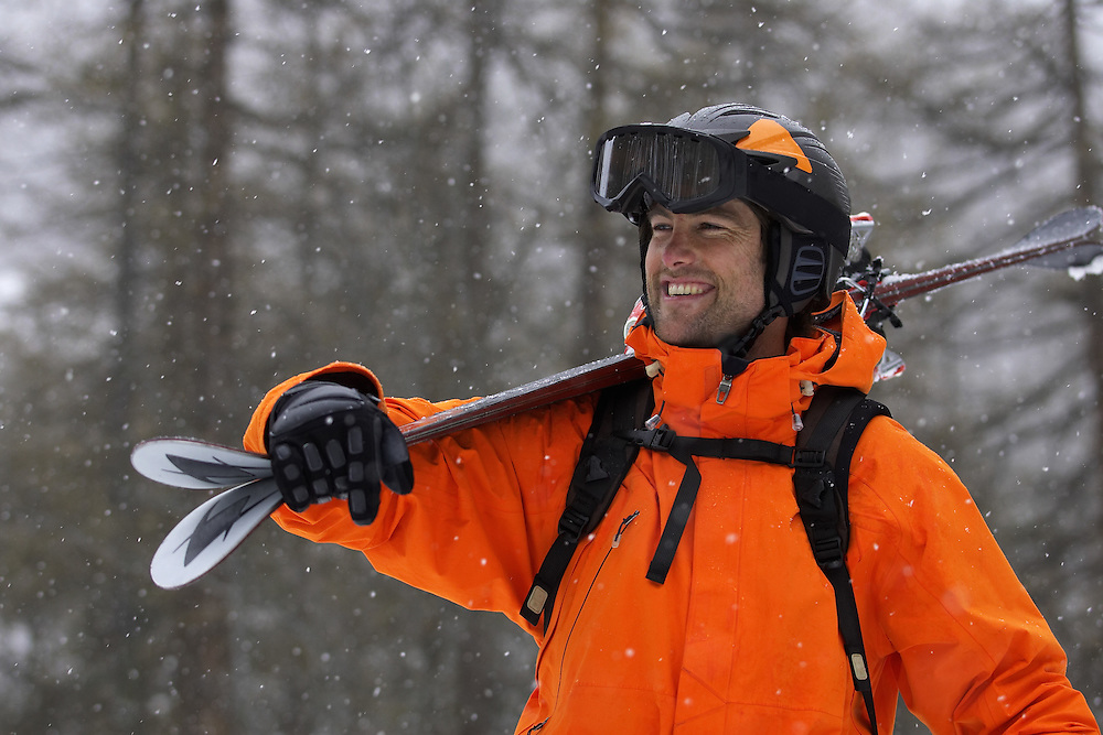 Winter Sports, male skier holding skis and smiling as it snows