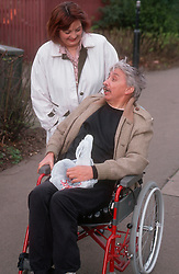 Carer talking to man with disability; who is manual wheelchair user; in street,