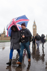 © Licensed to London News Pictures. 03/01/2016. London, UK. People with umbrellas walk past Big Ben on Westminster Bridge in London. London and the UK has experienced heavy rain and wind today. Photo credit : Vickie Flores/LNP