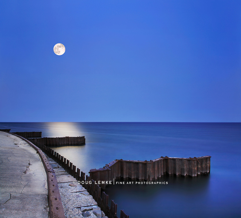 Night Meets Day As A Twilight Moon Spills Yellow Sunlight Down Over Dark And Serene Lake Michigan Waters At The Point Betsie Lighthouse Seawall Just Before Sunrise, Michigan's Lower Peninsula, USA