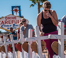 October 6, 2017 - Las Vegas, Nevada, U.S - LIZ HEALEY of Las Vegas rests her hand on the makeshift cross bearing the name of Thomas Day Jr. who was shot just feet from where Healey and her husband stood inside the Route 91 Harvest Music Festival near the front of the stage. This was Healey's first visit to the area since Sunday's mass shooting took place. It was the worst such incident in modern American history which claimed the lives of 59 people, including the killer Stephen Paddock, and injured hundreds of others. As pieces of Paddock's life are put together investigators are still searching for a motive. (Credit Image: © Nick Otto via ZUMA Wire)