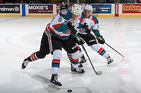 KELOWNA, CANADA - FEBRUARY 1: Andrei Grishakov #19 of the Calgary Hitmen is checked between Erik Gardiner #12 and Jack Cowell #8 of the Kelowna Rockets on February 1, 2017 at Prospera Place in Kelowna, British Columbia, Canada.  (Photo by Marissa Baecker/Shoot the Breeze)  *** Local Caption ***