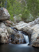 Water gently falls over granite boulders in Sabino Creek, Sabino Canyon, Tucson, AZ