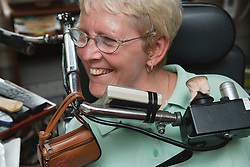 Woman with Cerebral Palsy with chin-operated wheelchair steering system.
