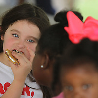 Bailey Drennan, 8, of Tupelo, and a Brownie, eats her S'More as she visits with friends a the National S'Mores Celebration Day held by the Girl Scouts Heart of the South at Ballard Park Friday night.