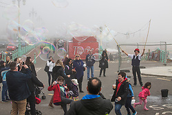 © Licensed to London News Pictures. 11/03/2017. Brighton, UK. A street performer entertains members of public on the Brighton promenade as a thick cloud of fog hangs over Brighton and Hove beach. Photo credit: Hugo Michiels/LNP