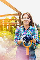 Portrait of mature gardener smiling while leaning on shovel