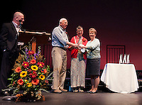 Bill and Lynne Burns receive the 2014 Hurst Award from Ellen Hurst with MC Warren Bailey on stage at the Winnipesaukee Playhouse Wednesday evening.  (Karen Bobotas/for the Laconia Daily Sun)