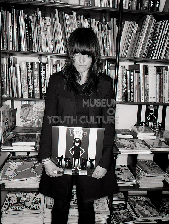 Young woman holding an Emily the Strange calendar and standing in front of bookshelves.