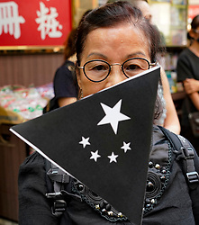 Hong Kong. 1 October 2019. Protestor at start of march with pro-democracy sign featuring black Hong Kong flag in Causeway Bay. Marchers were estimated at 100,000.  Violence later flared in the afternoon when protestors attacked police. Iain Masterton/Alamy Live News.