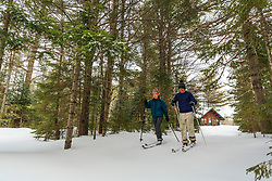 A couple cross country skiing outside Haskell Hut in Maine's Katahdin Woods and Waters National Monument.