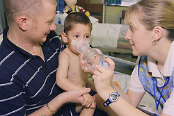 Staff nurse on children's renal ward teaching young boy how to use inhaler and spacer,