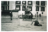 After the rain, a Tibetan Buddhist practitioner does his prostrations toward the Jokhang Temple in Lhasa.<br />