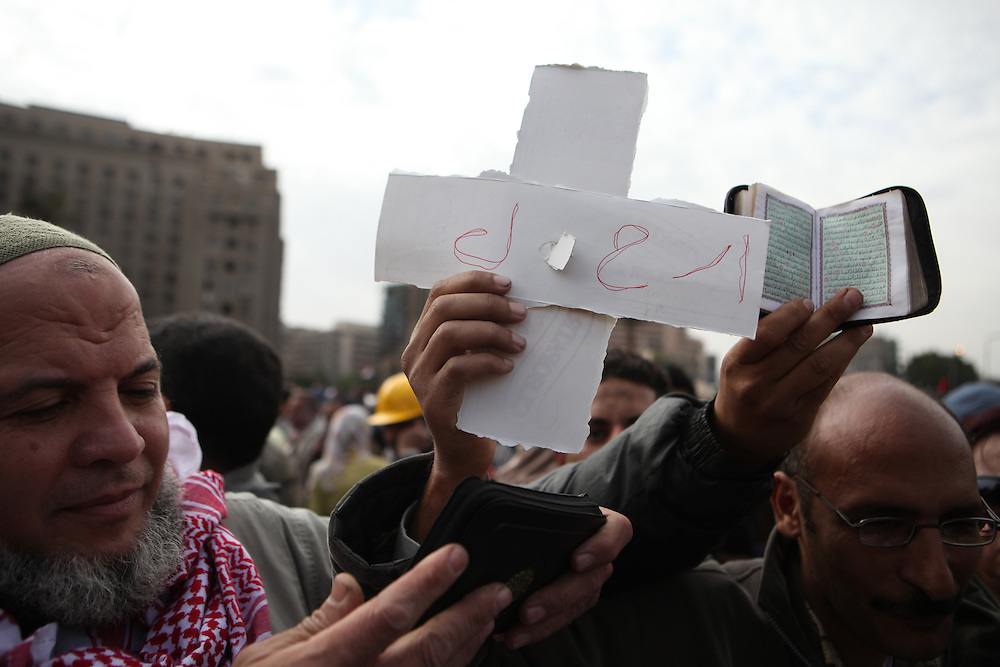 """At Tahrir Square, a Christian Egyptian holds a cross with the word """"irhal"""" (leave) written on it next to a Muslim Egyptian holding the Quran."""