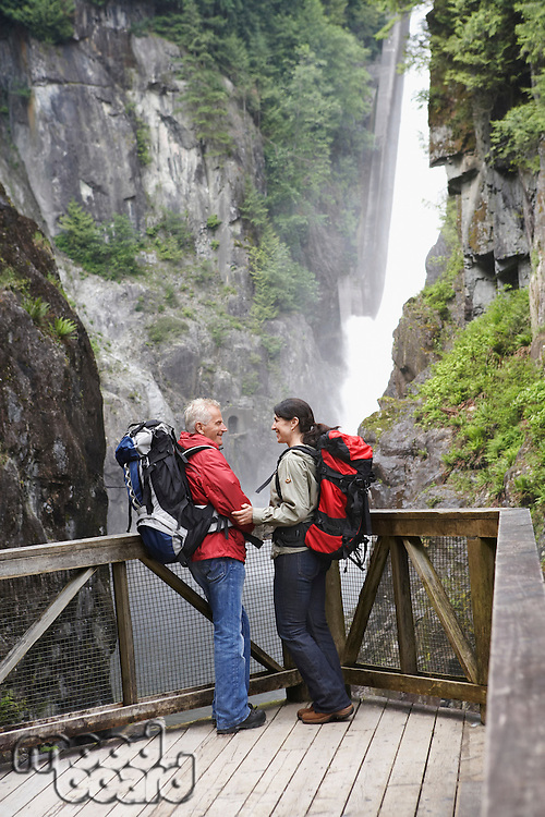 Man and woman in mountains near waterfall looking at each other