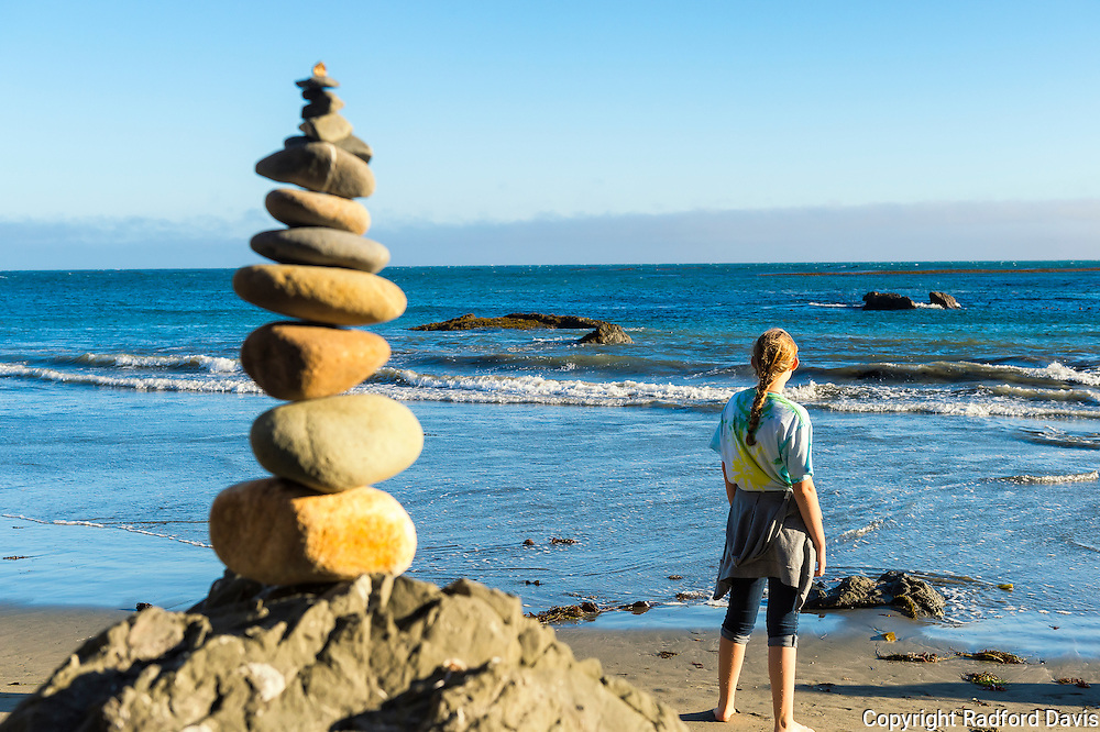 Girl and rock cairn on the beach in San Simeon, California, near sunset.