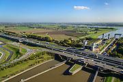 Nederland, Gelderland, Tiel, 24-10-2013; Betuweroute en autosnelweg A15 kruisen het Amsterdam-Rijnkanaal ter hoogte van de Prins Bernhardsluis,rivier de Waal in de achtergrond. Goederentrein nadert de brug over het kanaal. Binnenvaartschepen in de sluiskolk.<br /> Betuweroute, railway from Rotterdam to Germany,  and A15 motorway cross the Amsterdam-Rhine Canal at the Prince Bernhard lock, the Waal river in the background. Freight train on its way to the bridge over the canal. Barges in the lock chamber.<br /> luchtfoto (toeslag op standaard tarieven);<br /> aerial photo (additional fee required);<br /> copyright foto/photo Siebe Swart.