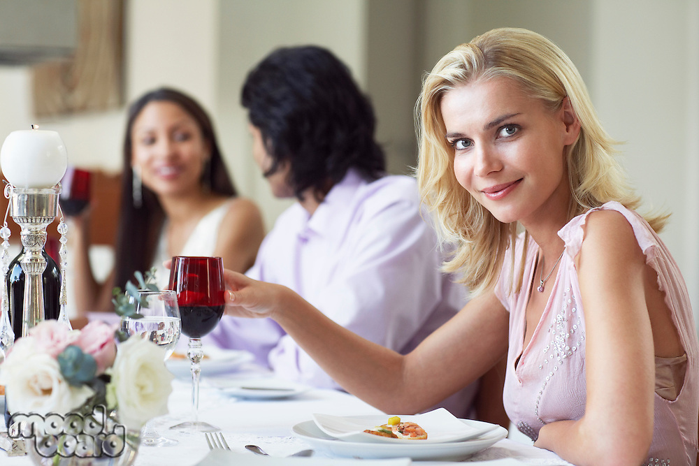 Young woman in dress sitting at table of formal dinner party