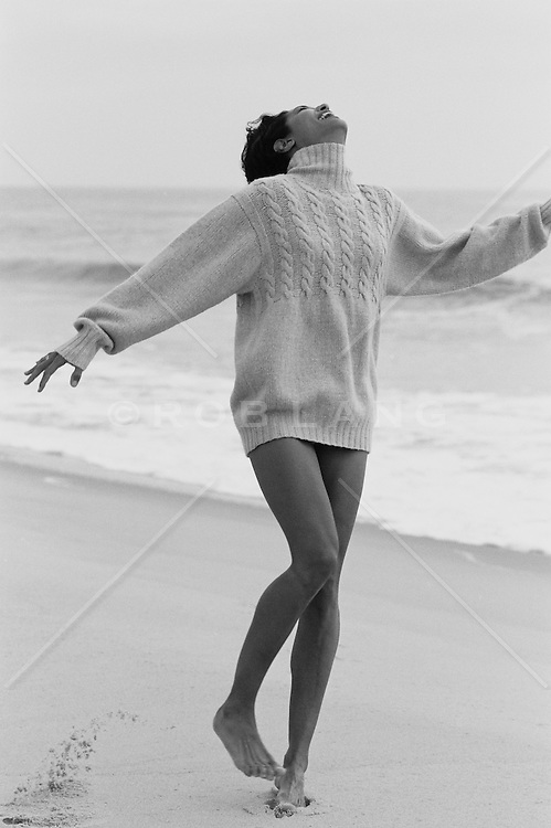Woman in a sweater enjoying the beach