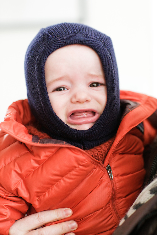7 month old baby boy crying in winter coat and hat