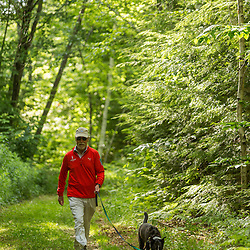 A man walks his dog on a trail near Page Pond in Meredith, New Hampshire.