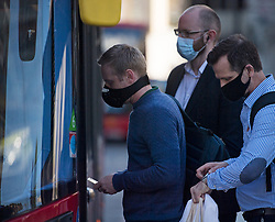 © Licensed to London News Pictures. 15/06/2020. London, UK. Commuters at Victoria Station in London board a bus, on the day the the easing of lockdown rules means all passengers must wear face masks. Government has introduced further measures to allow non-essential shops and services to reopen under social distancing conditions. Photo credit: Ben Cawthra/LNP