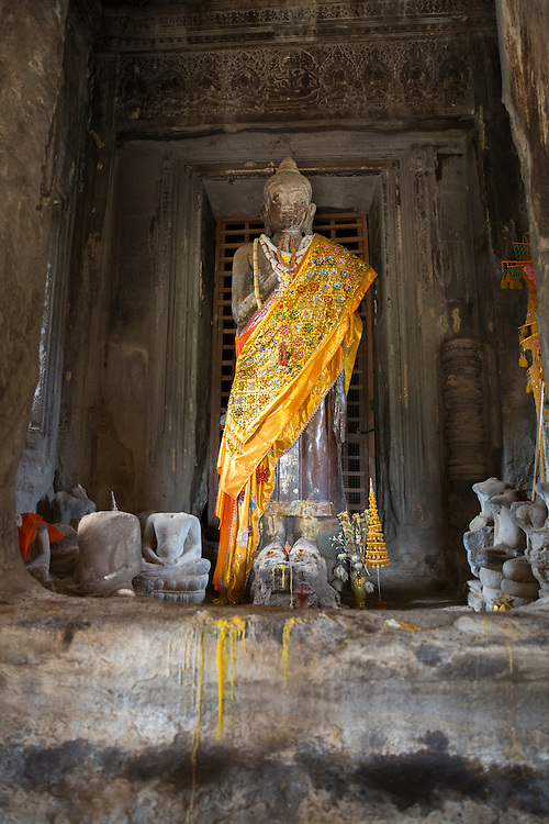An ancient Buddha statue decorated with yellow cloth within the Angkor Wat temple Siem Reap, Cambodia.  Angkor Wat is one of UNESCO's world heritage sites. It was built in the 12th century initially as a Hindu temple which then transformed into a Buddhist temple by the end of the 12th century. Theravada Buddhism has been the state religion in Cambodia since the 13th century.(photo by Andrew Aitchison / In pictures via Getty Images)