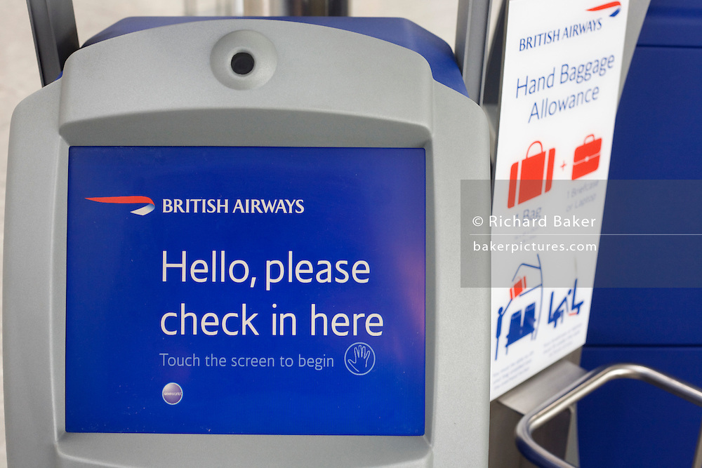 "A close-up detail of one of the British Airways' self-check-in kiosks in international check-in at Heathrow Airport's Terminal 5. A welcome message reads 'Hello, please check in here' and to the right is a guide for cabin baggage size allowance. The self-service kiosks that have been developed to allow customers to process their own ticketing on arrival at this aviation hub for British Airways. Once they've chosen their seat and printed a boarding pass, they can go straight to the Fast Bag Drop desk at the airport. There, baggage will be tagged by an agent and sent to the aircraft. At a cost of £4.3 billion, Terminal 5 has the capacity to serve around 30 million passengers a year. From writer Alain de Botton's book project ""A Week at the Airport: A Heathrow Diary"" (2009). ..."