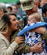 Specialist Beau Manning, of Watertown, talks to his daughter Braycen along with his girlfriend Breanna after arriving at the Huron Arena for the 153rd Engineer Battalion deactivation ceremony on Saturday morning in Huron. (Matt Gade / Republic)