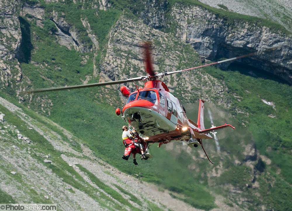 A helicopter rescues an injured hiker near Meglisalp. Berggasthaus Meglisalp can only be reached on foot in the spectacular heart of the Alpstein mountain chain in the Appenzell Alps, Switzerland, Europe. This authentic mountain hostelry, owned by the same family for five generations, dates from 1897. Meglisalp is a working dairy farm, restaurant and guest house surrounded by majestic peaks above green pastures.