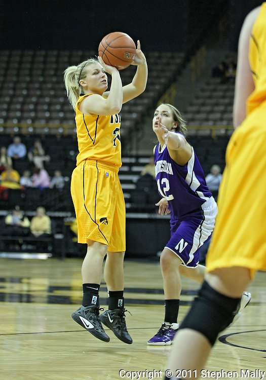 December 30, 2011: Iowa Hawkeyes guard Melissa Dixon (21) puts up a shot as Northwestern Wildcats guard Karly Roser (42) tries to block during the NCAA women's basketball game between the Northwestern Wildcats and the Iowa Hawkeyes at Carver-Hawkeye Arena in Iowa City, Iowa on Wednesday, December 30, 2011.