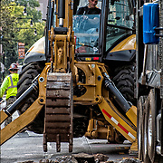 Backhoe operator excavating and lifting and moving material soil to fill in underground street repairs replacing old water pipes.