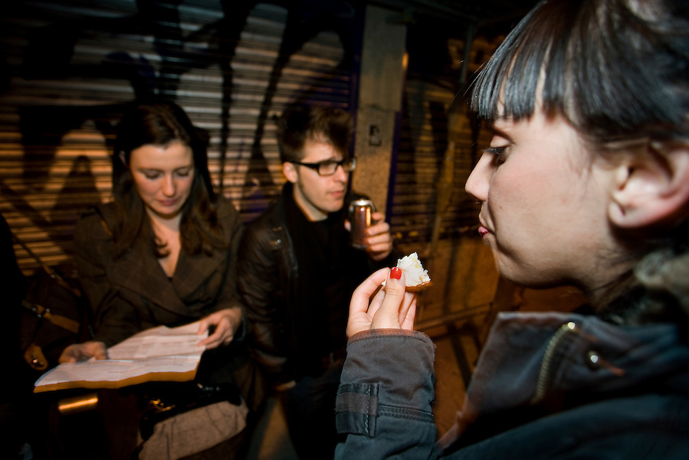 "6:12 AM: María Padín, 25, Fermín Álvarez López, 25, and Ángela Hermosa, 23, take a snack at the gate of ""Sala Sol"" club in Madrid.."