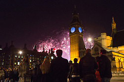 © Licensed to London News Pictures. 01/01/2016. London, UK. People in Parliament Square watch fireworks explode behind Big Ben to mark the start of the New Year, 2016 Photo credit : Vickie Flores/LNP