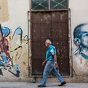 An elderly man walks past a doorway and graffiti and wall art on the street in Havana