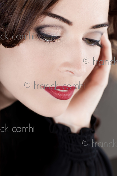 Closeup portrait of a beautiful middle aged woman with red lips looking down