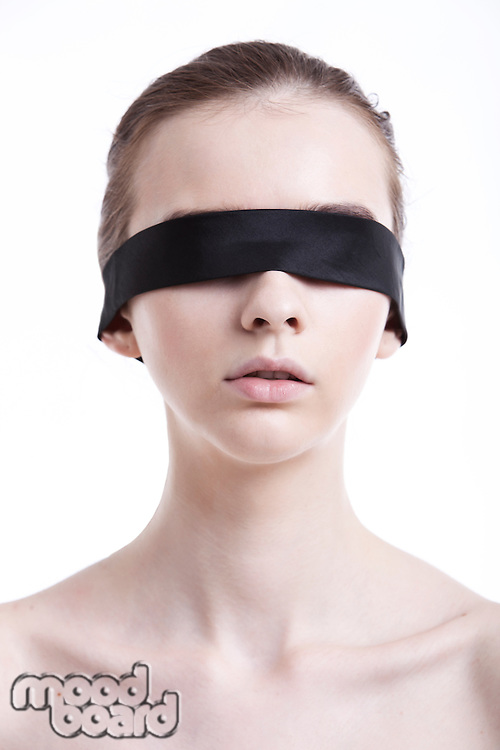 Shirtless young woman blindfolded against white background