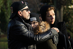 Highgate, London, December 26th 2016. Fans gather outside the London home of pop icon George Michael who died on Christmas day. PICTURED: A grief-stricken family hold each other outside Michael's London home.