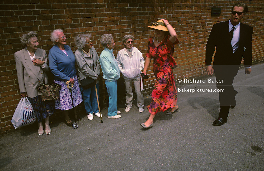 Five elderly women on-lookers are lined against a wall outside the famous Ascot race course on Ladies' Day, the annual event on the English sporting and social calendar in June. Each are standing in order of size, from tallest (who holds a Tesco supermarket bag) to smallest and watch as two posh couples arrive for the day's racing dressed in showy dresses for the ladies and the men in formal top hat and tails. The posh lady in the front is in yellow and holds on to her straw hat on this windy summer day. Each wears their red Ascot badges allowing them entry to this exclusive royal event attended by the Royal Family and the hoi polloi of English society. We see the two sides of the class system but it is a humerous scene. There is good nature between the two groups with smiles exchanged with one couple but discomfort from those behind.