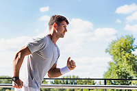 Portrait of young attractive man running in park