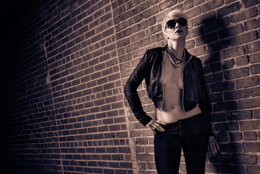 Beautiful, sexy woman in black leather and pants in an alley