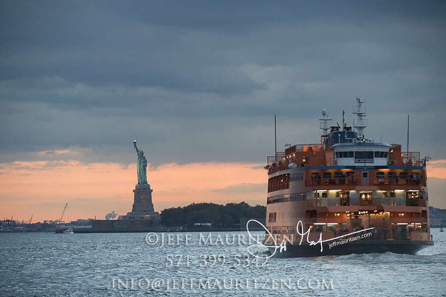 The Staten Island Ferry crosses the Hudson River past the Statue of Liberty going from Manhattan to Staten Island, NYC.